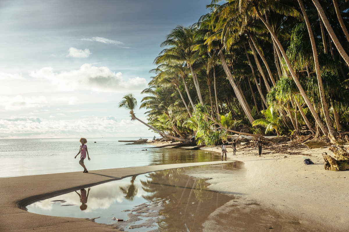 A child walks on a beach that is rapidly being inundated by the relentlessly rising tides
